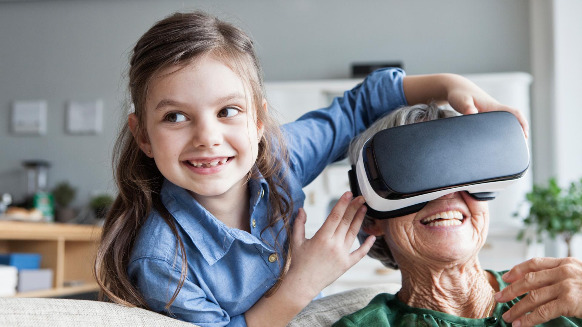 Ein Mädchen und eine ältere Frau, die eine VR-Brille trägt. Beide lachen.