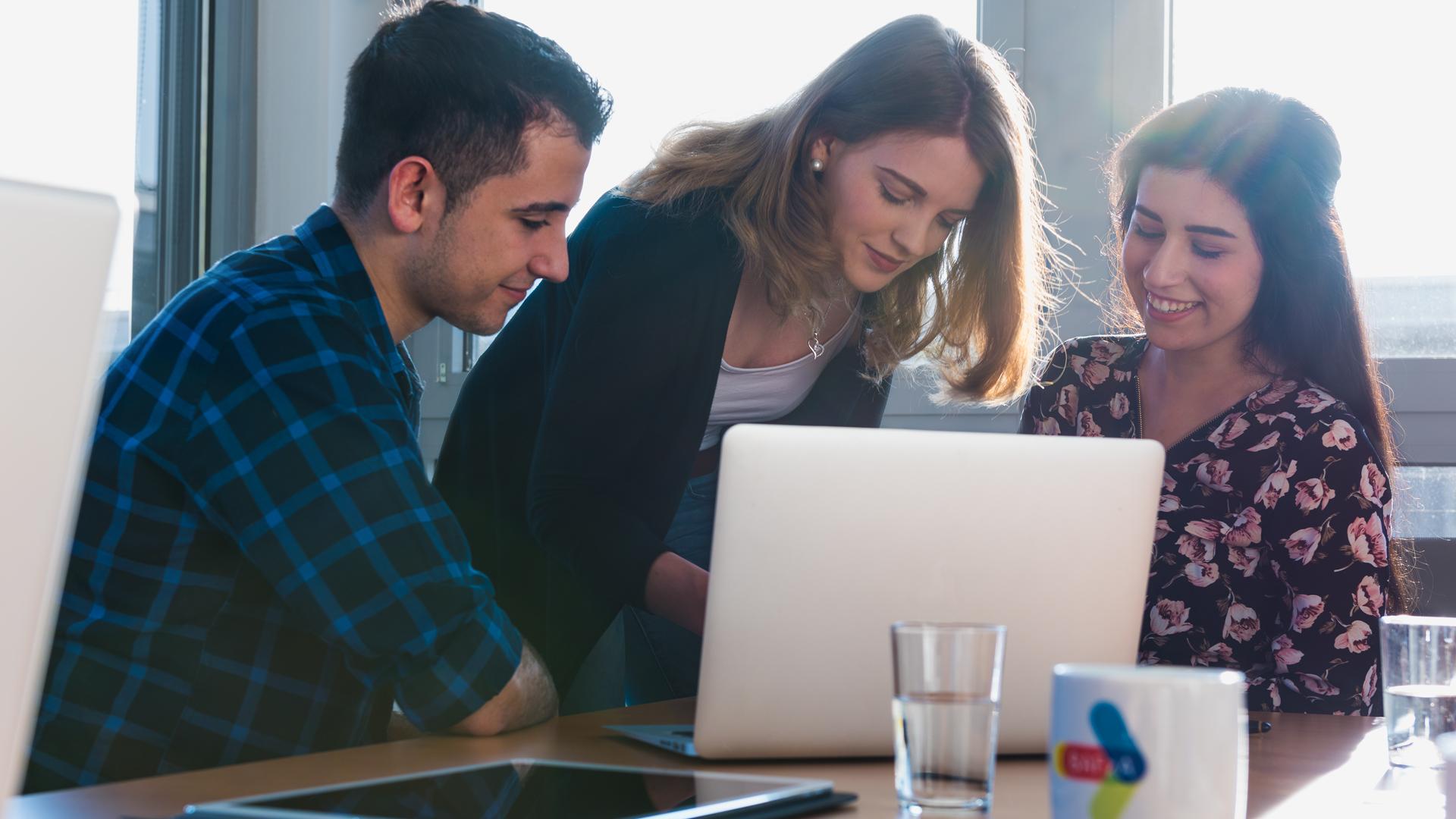 Im Büro: Zwei junge Mitarbeiterinnen und ein junger Mitarbeiter sind um einen Laptop versammelt.