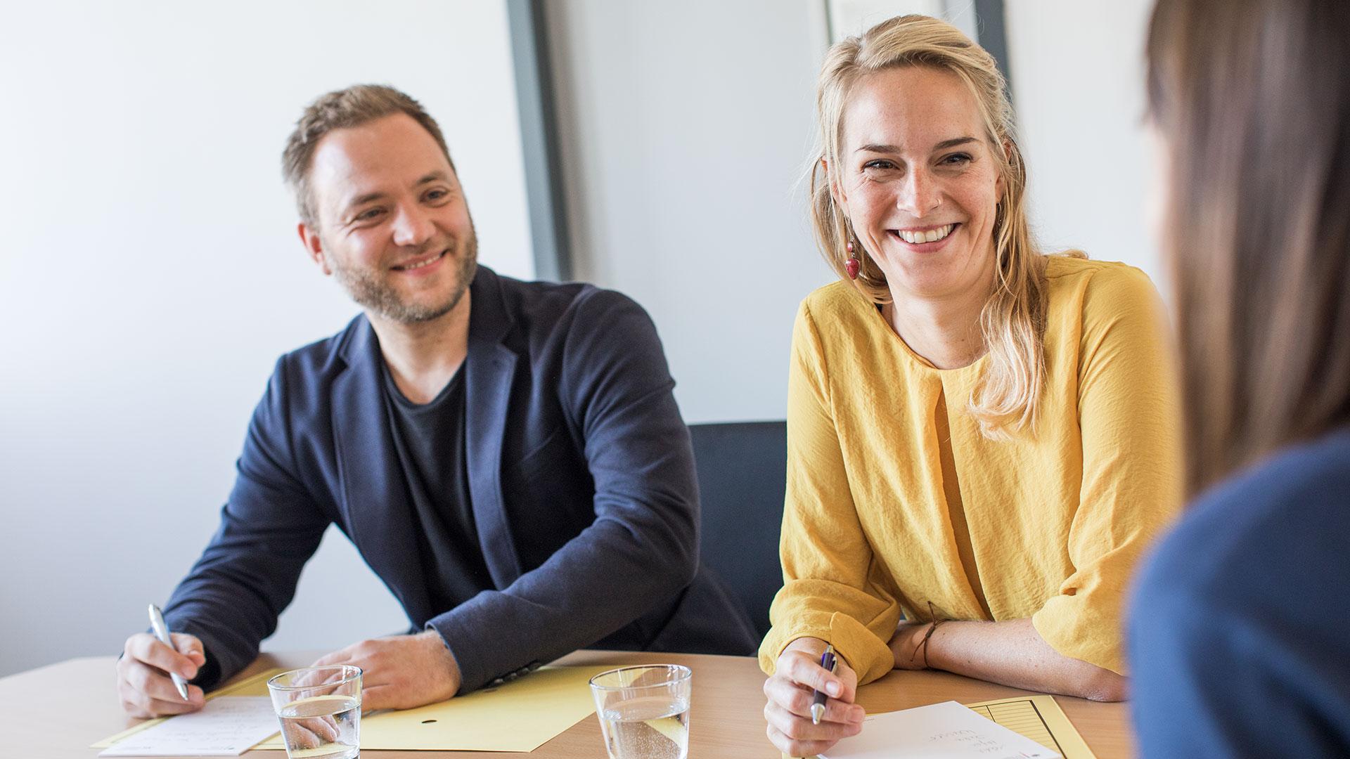Eine Bewerbungssituation. An einem Tisch sitzen sich zwei Mitarbeiter, ein Mann und eine Frau, und eine junge Bewerberin gegenüber. Die Personen lächeln.