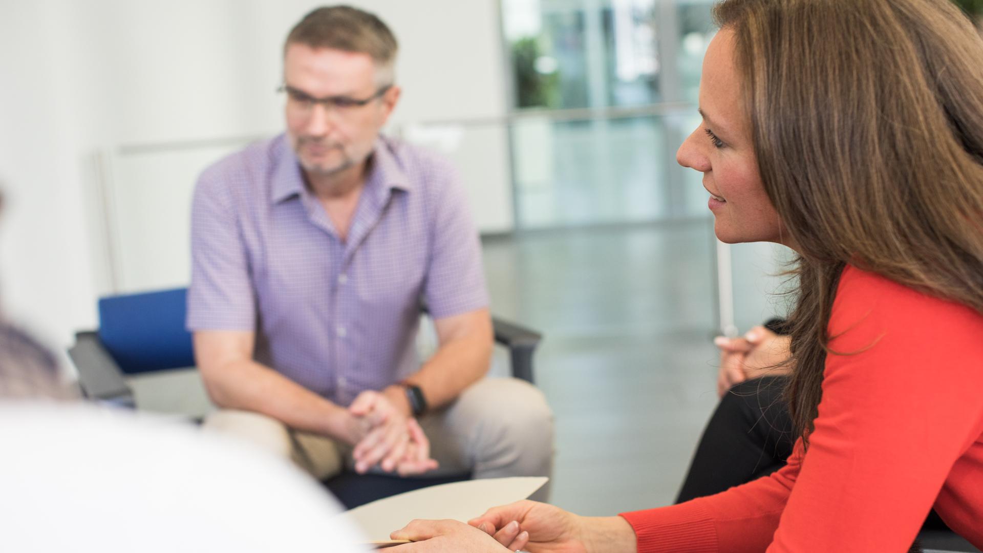 Eine Gesprächssituation: mehrere Mitarbeiter und Mitarbeiterinnen sitzen zusammen und unterhalten sich angeregt.