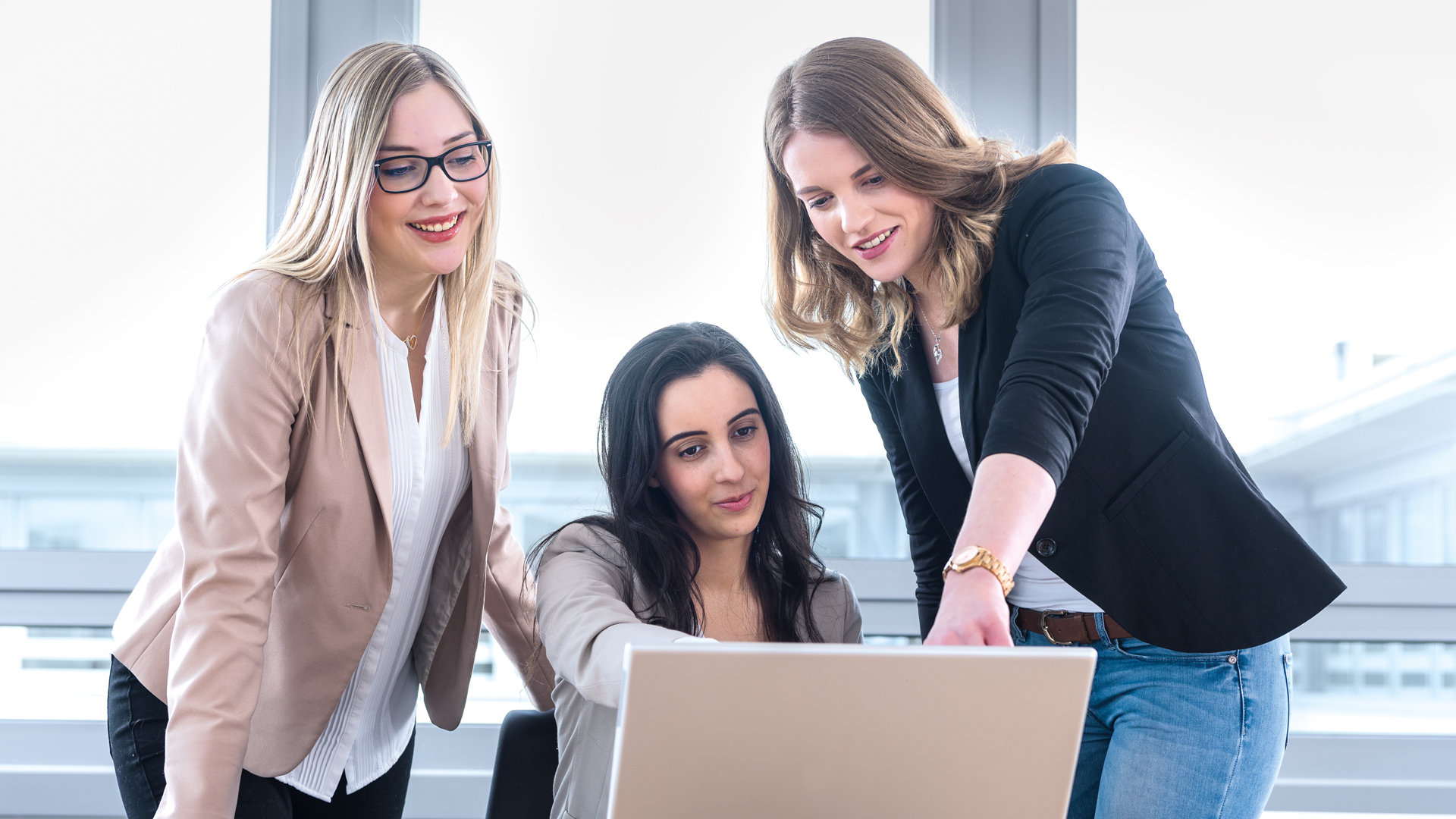 Im Büro: Drei junge Mitarbeiterinnen sind um einen Laptop versammelt.