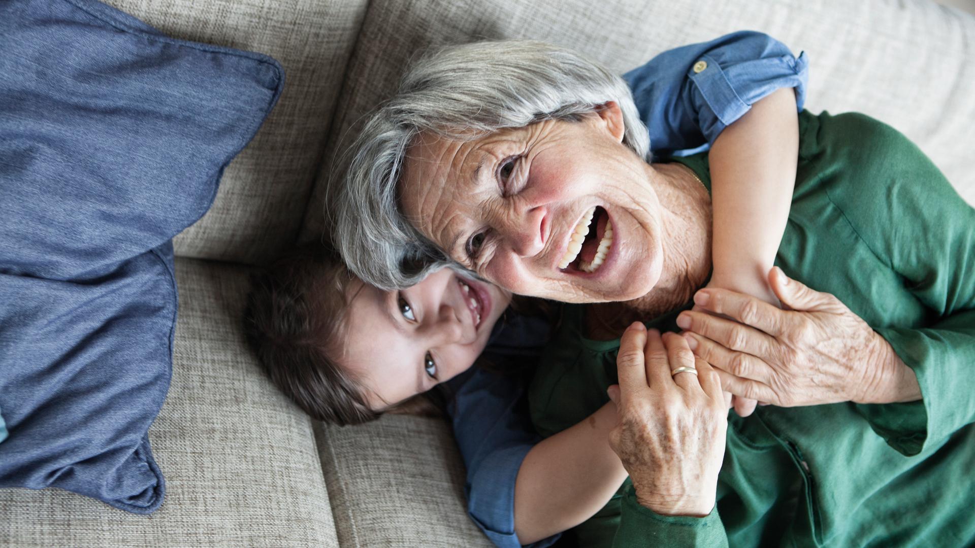 Eine ältere Frau und ein Mädchen - vielleicht ihre Enkelin - umarmen sich auf einem Sofa liegend. Beide haben Spaß und lachen.
