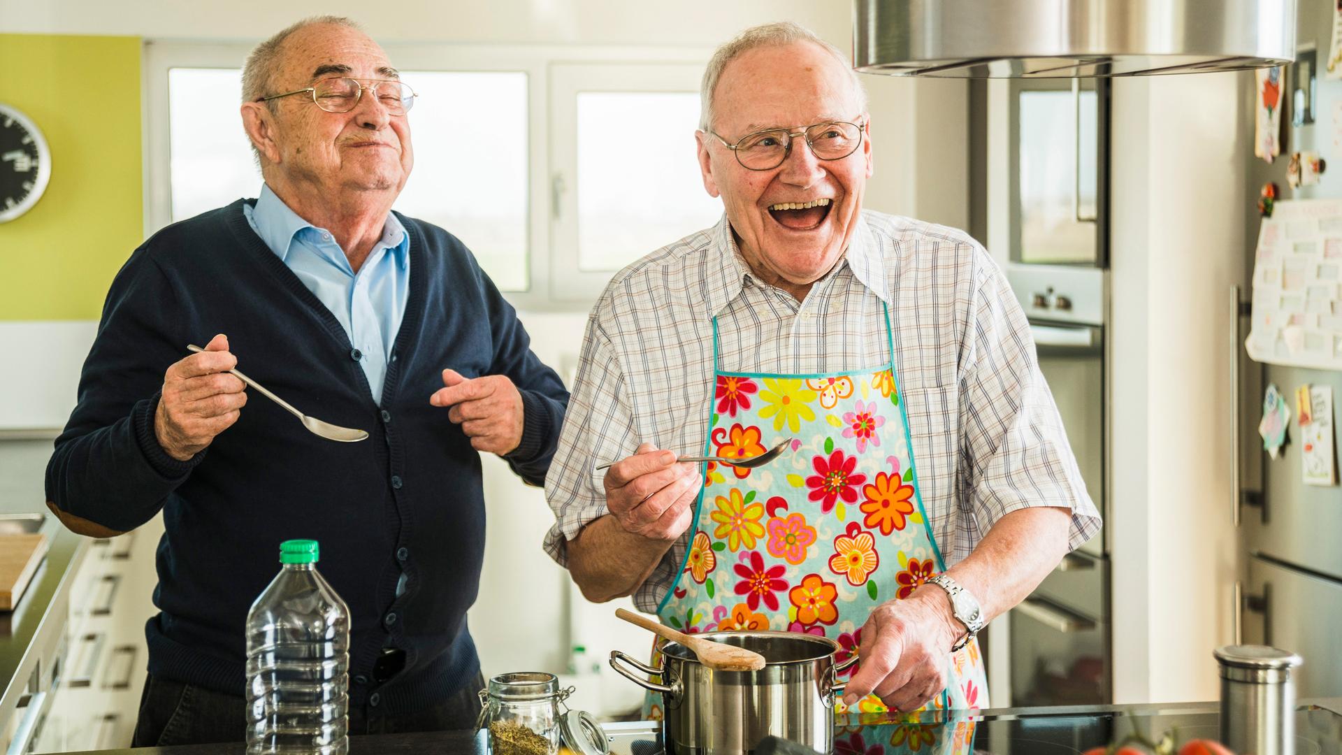 Zwei ältere Männer beim Kochen in der Küche. Beide lachen fröhlich.