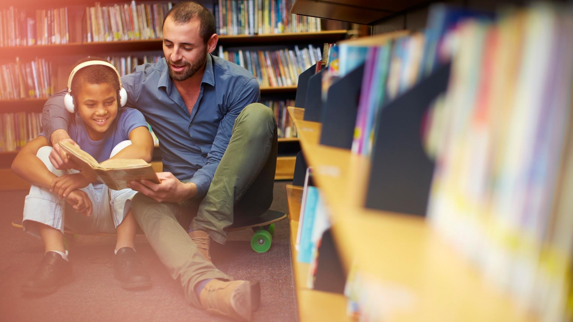 Ein junger Mann und ein Junge sitzen nebeneinander auf dem Boden einer Bibliothek.