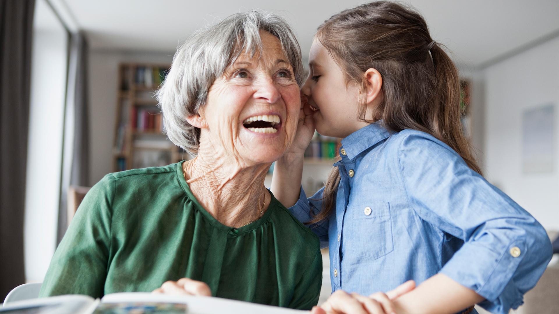 Eine ältere Frau und ein kleines Mädchen, vielleicht ihre Enkelin. Das Mädchen flüstert der älteren Frau etwas ins Ohr, sie lacht laut auf.