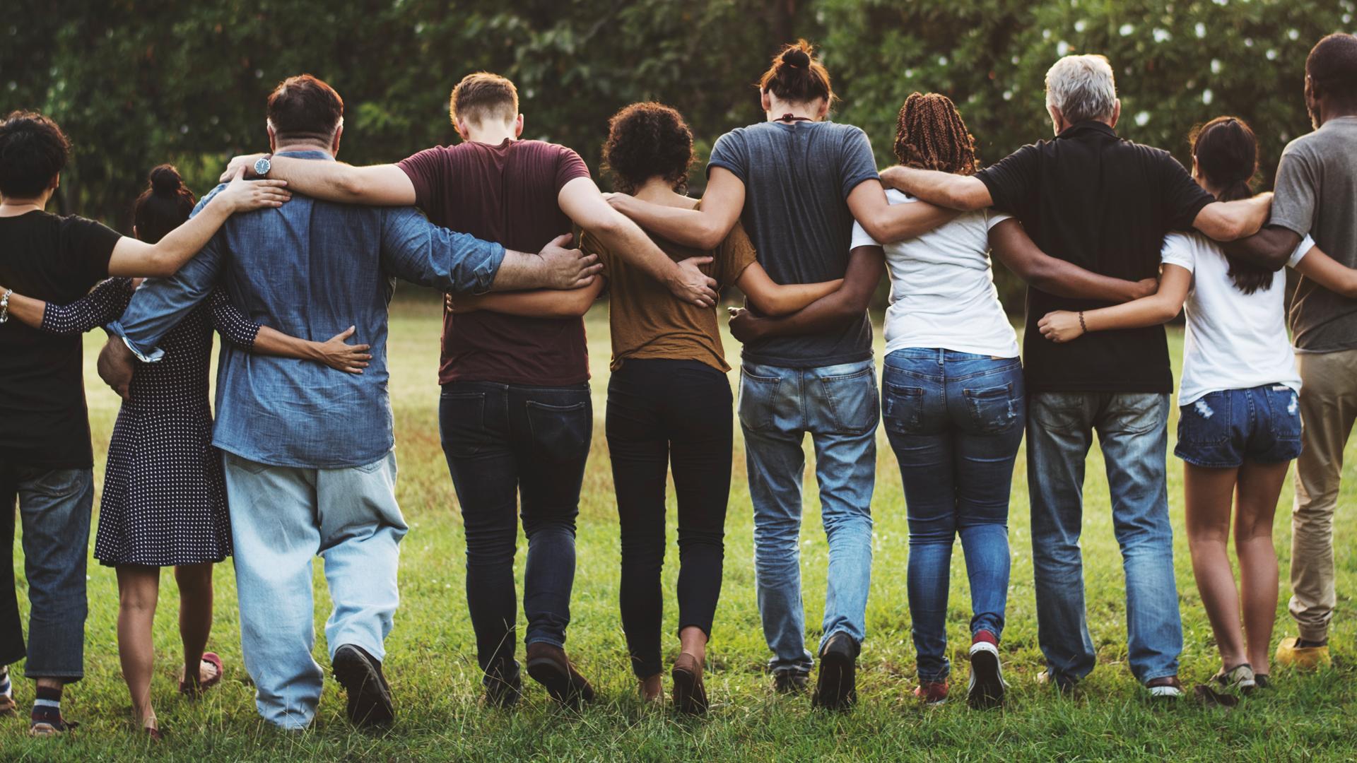 Eine Menschenkette von hinten - die jungen Leute haben sich die Arme über die Schultern gelegt und gehen vorwärts über eine Wiese.
