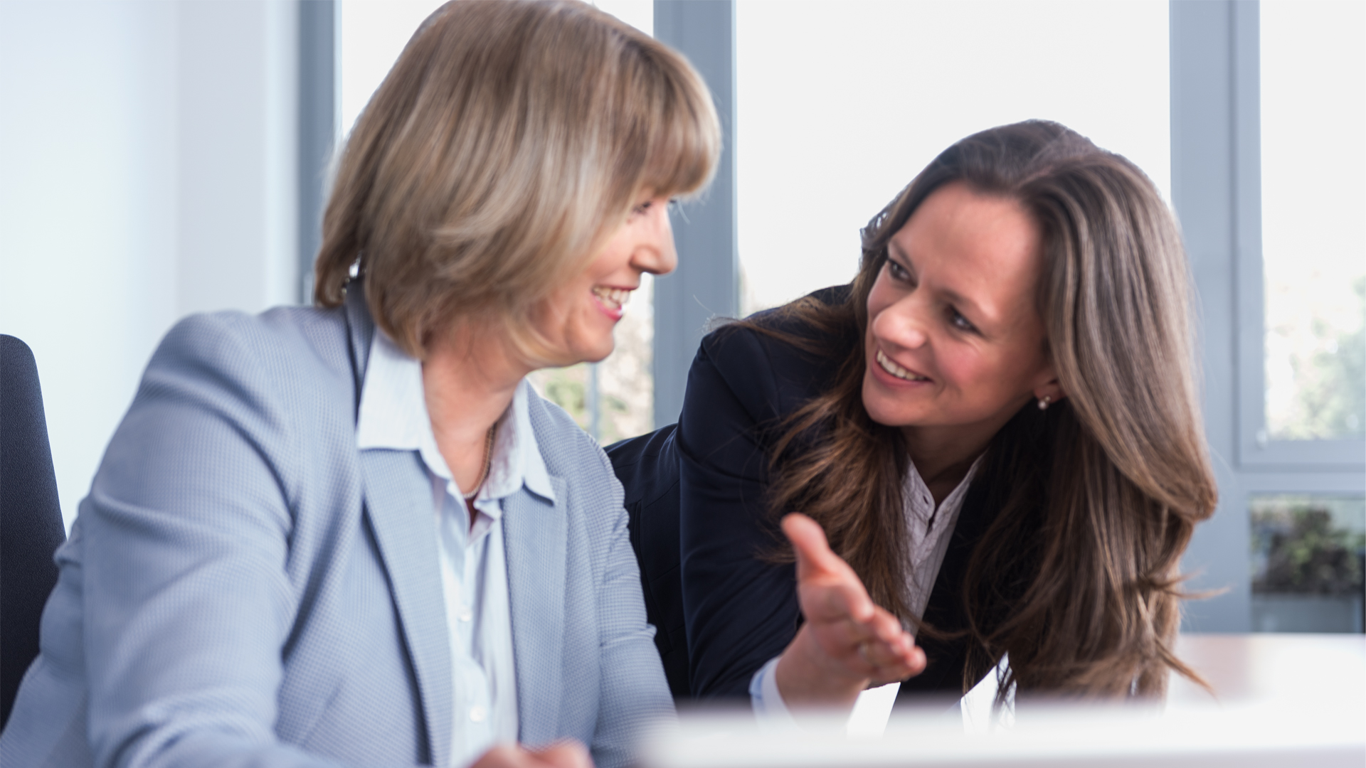 Im Büro: Zwei Frauen in einer Gesprächssituation. Im Vordergrund sieht man den Rand eines Bildschirms.