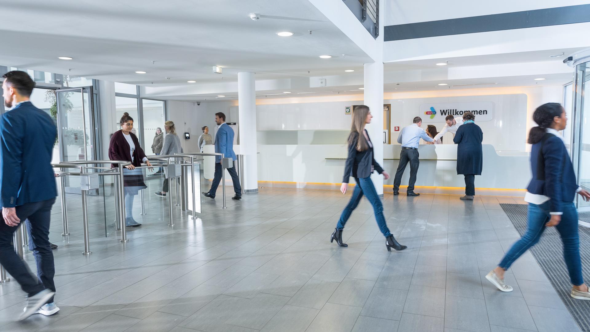 Im Empfangsbereich der BAFzA-Zentrale: In der hellen, modernen Eingangshalle kommen und gehen Menschen.