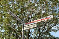 Im Vordergrund drei Straßenschilder. Nach rechts zeigend das Schild An den Gelenkbogenhallen, mit einem roten Querbalken durchgestrichen, sowie das Schild Von-Gablenz-Straße. Nach links zeigend das Schild An den Gelenkbogenhallen ohne Querbalken. Den Hintergrund bilden Äste und Blätter eines Baumes