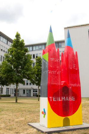 Im Vordergrund steht eine bunte Skulptur, im Hintergrund steht ein großes Gebäude.