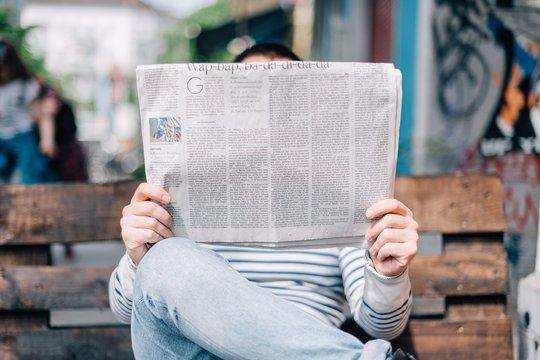 Eine Person sitzt auf einer Bank und liest eine Zeitung. Die Zeitung wird so gehalten, dass sie das Gesicht der Person verdeckt.
