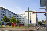 In der Mitte das Gebäude des Bundesamtes, am rechten Bildrand zwei Straßenschilder. Das bisheriger Schild der Von-Gablenz-Straße sowie das neue Schild An den Gelenkbogenhallen mit rotem Querbalken durchgestrichen.